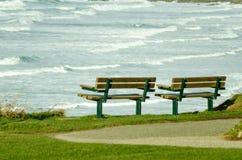 Zwei leere Park-Bänke, die Seeansicht betrachten Stockbild