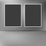 Zwei leere Rahmen, die an der Wand mit Zusammenfassung hängen, verwischten backg Stockfotos