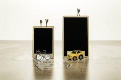 Zwei leere schwarze Bretter mit kleinem menschlichem Modell mit Auto und Fahrrad auf Weltkarte Lizenzfreie Stockfotos