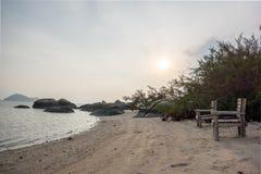 Zwei leere Stühle auf einem überschüssigen Strand im Sonnenuntergang Stockfotos