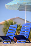 Zwei leere Stühle stehen unter Strandregenschirm Lizenzfreie Stockfotos