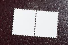 Zwei leere Stempel auf einem roten ledernen Hintergrund Stockbilder