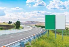Zwei leere Verkehrsschilder nähern sich Landstraße Stockfotos