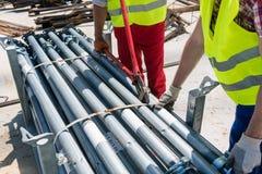 Zwei leistungsfähige Arbeitskräfte, die ein metallisches Baugerüst errichten Lizenzfreies Stockbild