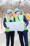 Zwei leitende Ingenieure oder Geschäftsmänner, die Baustelle, Pläne und die Diskussion betrachtend besichtigen stockfotografie