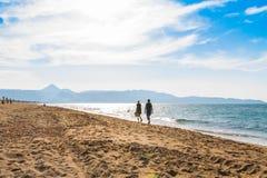 Zwei Leute, die auf den Strand durch das Meer über dem Himmelklarheitsweg der Küste sonniger Tagesgehen stockfotografie