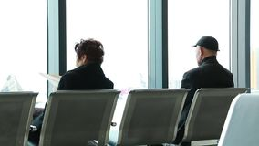 Zwei Leute, die auf der Bank im Flughafen sitzen stock video