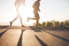 Zwei Leute, die auf Landstraße bei Sonnenaufgang laufen Lizenzfreie Stockfotografie