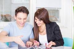 Zwei Leute, die an der Tabellenlesezeitschrift sitzen Stockfotos
