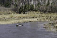 Zwei Leute, die in ein Gummiboot auf dem Fluss schwimmen lizenzfreie stockbilder
