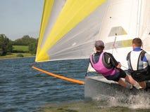 Zwei Leute, die ein kleines graues Schlauchboot auf einem See segeln Lizenzfreies Stockfoto
