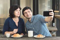 Zwei Leute, die ein Selfie an einem Café im Freien nehmen Stockfotografie