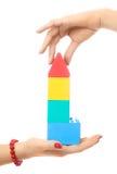 Zwei Leute, die ein Spielzeughaus bilden stockbilder