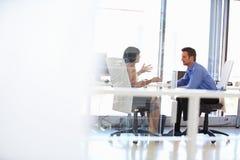 Zwei Leute, die in einem Büro sprechen Lizenzfreie Stockbilder