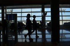 Zwei Leute, die am Flughafen hintergrundbeleuchtet gehen Lizenzfreie Stockfotos