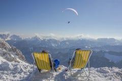 Zwei Leute, die Getränk beim Aufpassen des Gleitschirms über österreichischen Alpen vorschreiben stockfotografie
