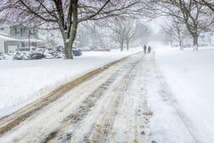 Zwei Leute, die hinunter eine Landstraße im Blizzard gehen, stürmen Lizenzfreie Stockfotografie