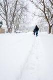 Zwei Leute, die hinunter eine Landstraße im Blizzard gehen, stürmen Stockfotografie