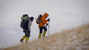 Zwei Leute, die langsam auf einer Steigung im Winter wandern stock footage