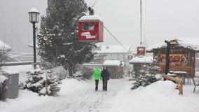 Zwei Leute, die unter schwere Schneefälle gehen stock video