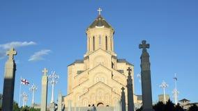 Zwei Leute gehen zum Eingang der Kathedrale Tiflis-Heiliger Dreifaltigkeit, Sameba Auf jeder Seite der Flaggen, die im Wind flatt stock footage