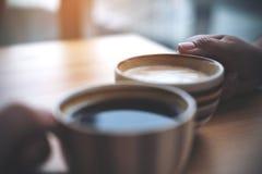 Zwei Leute klirren Kaffeetassen auf Holztisch im Café Lizenzfreies Stockfoto