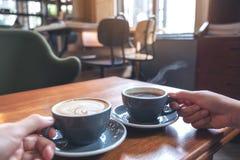 Zwei Leute ` s übergibt das Halten von Schalen des Kaffees und der heißen Schokolade auf Holztisch im Café lizenzfreie stockfotografie