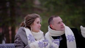 Zwei Liebhaber, die auf einer Bank im Winter Park sitzen Sie halten Becher Kaffee und schauen irgendwo zur Seite stock video footage