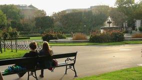 Zwei Liebhaberfreunde setzen im grünen Stadtpark nahe Brunnen auf die Bank stock footage
