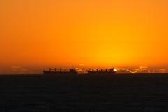 Zwei Lieferungen und ein orange Sonnenuntergang stockfotografie