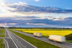 Zwei LKWs auf der Landstraße, die yelow Felder durchläuft stockbild