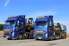 Zwei LKWs Volvos FH13, die Ponsse-Forstwirtschafts-Maschinerie schleppen Stockfotos