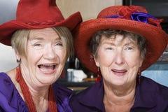 Zwei ältere Frauen, die rote Hüte tragen Stockbild