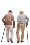 Zwei ältere Menschen, die mit den Stöcken lokalisiert auf weißem backgrou gehen Stockfoto