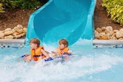 Zwei lustige aufgeregte Kinder, die Sommerferien im WasserVergnügungsparkreiten auf Dia mit Floss genießen Glückliches kleines stockfotografie