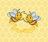 Zwei lustige Bienen auf dem Bienenwabenhintergrund Stockfoto