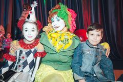 Zwei lustige Clowne werden mit einem Jungen fotografiert stockfotografie