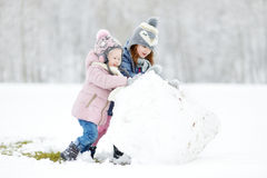 Zwei lustige entzückende kleine Schwestern im Winterpark Stockfotografie