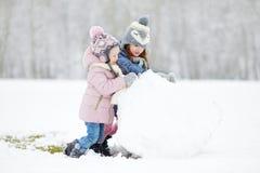 Zwei lustige entzückende kleine Schwestern im Winterpark Lizenzfreie Stockfotos
