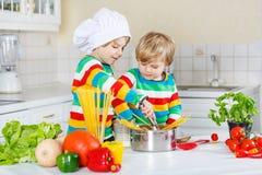 Zwei lustige Freunde, die italienische Mahlzeit mit spahetti kochen lizenzfreie stockbilder
