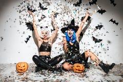 Zwei lustige junge Frauen in ledernem Halloween kostümiert die Aufstellung Stockbild