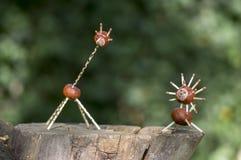 Zwei lustige Kastanientiere auf Baumstumpf, grüner Hintergrund, traditioneller Herbst handcraft, Löwe und Giraffe Stockfotos