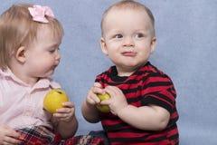 Zwei lustige Kinder, die mit Äpfeln spielen Retro- Art Lizenzfreie Stockfotos