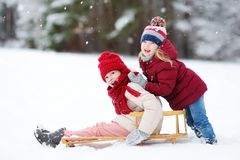 Zwei lustige kleine Mädchen, die Spaß mit einer Trickserei im schönen Winterpark haben Nette Kinder, die in einem Schnee spielen stockfotos