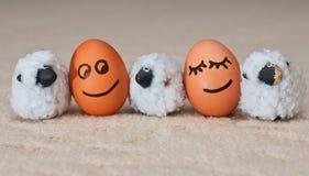 Zwei lustige lächelnde Eier nahe kleine Schafe lizenzfreie stockbilder