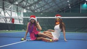 Zwei lustige Mädchen sitzen auf dem Tennisplatz in den Zusätzen des neuen Jahres stock video footage