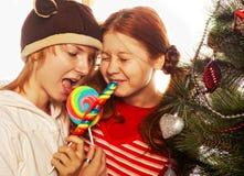 Zwei lustige Mädchen mit Lutschbonbon-springen heraus. Lizenzfreies Stockfoto