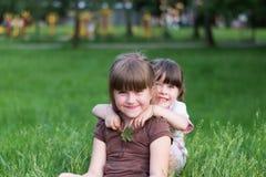 Zwei lustige Schwestern auf dem Gras lizenzfreies stockbild
