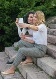 Zwei Mädchen nehmen selfies und essen Eiscreme stockbild