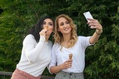 Zwei Mädchen nehmen selfies und essen Eiscreme stockbilder
